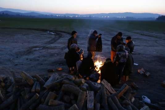 Des réfugiés se réchauffent autour d'un feu près du village frontière d'Idomeni en Grèce le 21 janvier 2016.