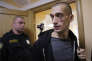 FILE - In this Sept. 16, 2015, file photo, Russian performance artist Pyotr Pavlensky, right, exits a court room after a hearing on his case in St. Petersburg, Russia. The partner of Russian dissident best known for his politically charged performance art - including nailing his scrotum to Red Square - said he has been transferred to a psychiatric hospital. Pavlensky's partner, Oksana Shalygina, told The Associated Press on Thursday, Jan. 28, 2016, that the artist was transferred the previous day from jail to a psychiatric hospital for evaluation, lasting up to 21 days. (AP Photo/Dmitry Lovetsky, File)