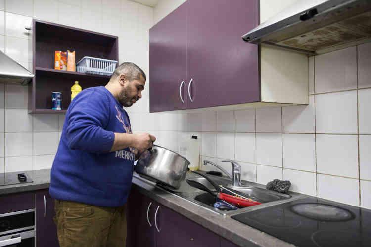 Samuel, hébergé par les Enfants du Canal, fait une partie de la vaisselle à la fin du repas.