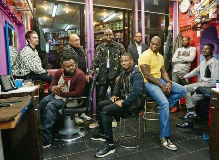 """Babs (au centre) et Gaye (à gauche) dans le salon Lucky Coiffure du Xe arrondissement de Paris, où le réalisateur-photographe Hugues Lawson-Body capte sur le vif les débats animés des clients pour sa mini-série le """"Barber Show""""."""