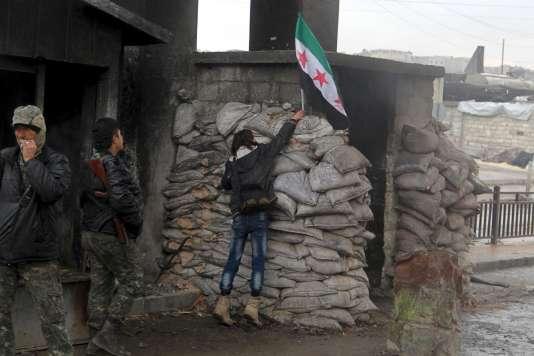 Une manifestante pour la libération des prisonniers des prisons gouvernementales syriennes dépose le drapeau de l'opposition sur un point de contrôle surveillé par l'Armée syrienne libre à Alep, le 24janvier.