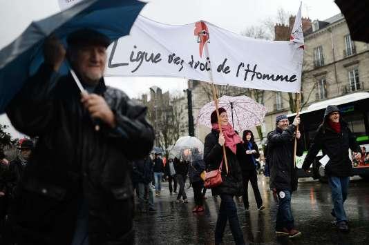 """""""Des abus ont été commis par les forces de police. En particulier des interventions violentes fondées sur des informations incorrectes ont causé une grande souffrance morale et des dommages matériels lourds chez des personnes n'ayant aucun lien avec le terrorisme (Photo: femme porte une banderole de la Ligue des droits de l'homme, le 30 janvier à Nantes, lors d'une manifestation contre l'état d'urgence)."""