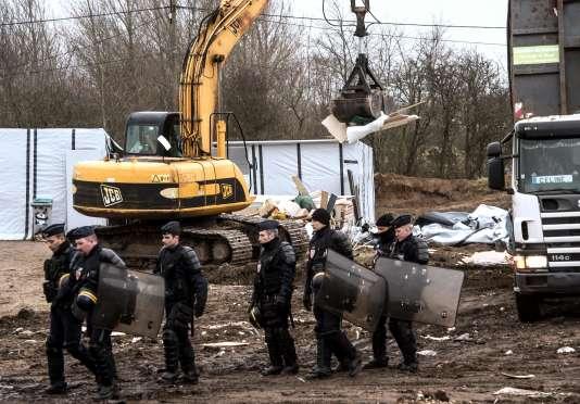 """Des CRS passent devant un bulldozer démolissant des structures de la """"jungle"""" de Calais, comprenant notamment une mosquée et une église évangélique."""
