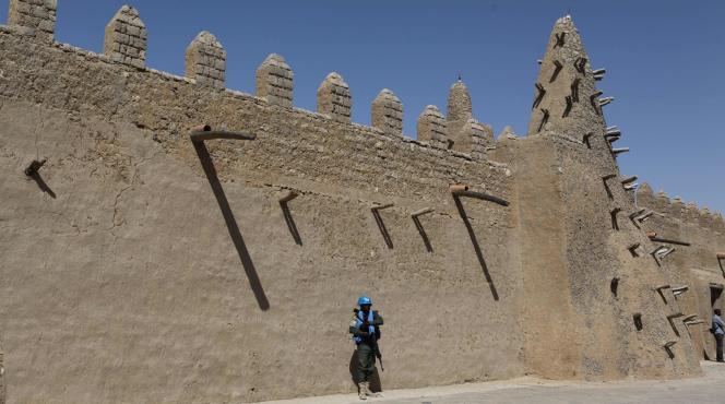 Un casque bleu de l'ONU devant la mosquée de Djingareyber à Tombouctou, au Mali, reconstruite notamment grâce à l'aide de l'Unesco. La cité est désormais interdite aux touristes français, par décision du Quai d'Orsay.
