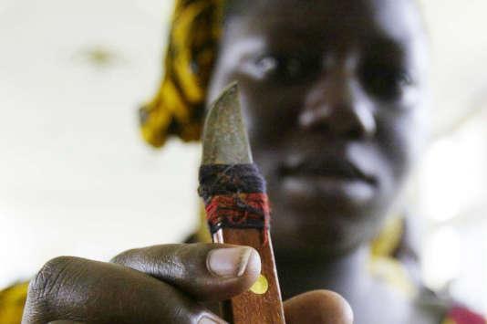 Une femme tient un outil utilisé pour exciser, lors d'un rassemblement pour dénoncer cette pratique de mutilation génitale à Abidjan en Cote d'Ivoire, en 2005.