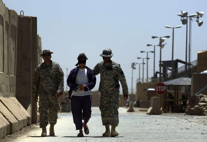 Des soldats américains escortent un détenu irakien dans le camp de détention de Cropper à Bagdad en 2008.