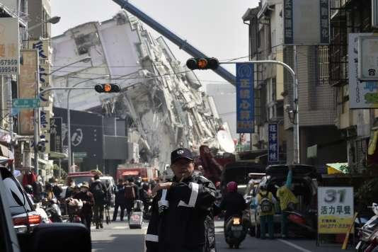 Dans la rue, devant un ensemble résidentiel de la ville de Tainan qui s'est effondré lors du séisme du 6 février à Taïwan.