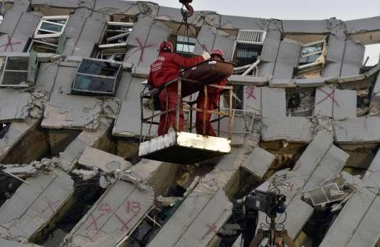Secours dans les décombres d'un ensemble résidentiel de Tainan, dimanche 7 février, après le séisme de samedi à Taïwan.