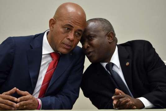 Le président haïtien, Michel Martelly (à gauche), s'entretient avec Cholzer Chancy, président de la Chambre des députés, au cours de la cérémonie entérinant l'installation d'un gouvernement de transition, samedi 6 février, à Port-au-Prince.