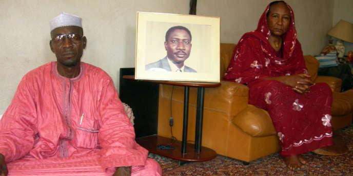 La veuve d'Ibni Oumar Mahamat Saleh, Sadia Brahim et son cousin Moussa Mahamat Saleh, posant, le 15 mai 2008, avec le portrait de l'opposant tchadien disparu.