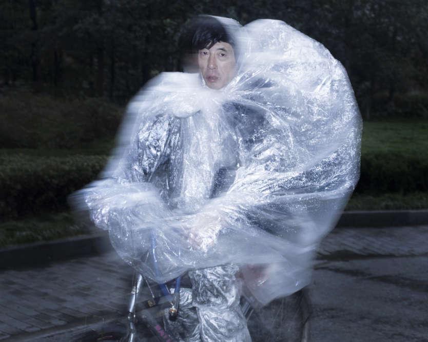 """«Pour réaliser la série """"Short Flashes"""", véritable album de portraits, Wiktoria Wojciechowska a figé les cyclistes chinois dans une posture identique reflétant une certaine image de la Chine. Tous sont sous la pluie, la nuit, enveloppés dans des capes en plastique.»"""