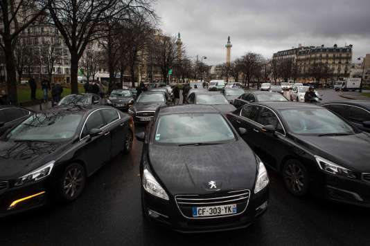 "Uber and other ride-hailing companies, known in France as ""voitures de tourisme avec chauffeur"" (VTC), a class of companies that allow passengers to book rides with independent professional chauffeurs, gather as they block the roundabout at Place de la Nations to protest against the LOTI law in Paris, on February 9, 2016.      / AFP / Geoffroy Van der Hasselt"