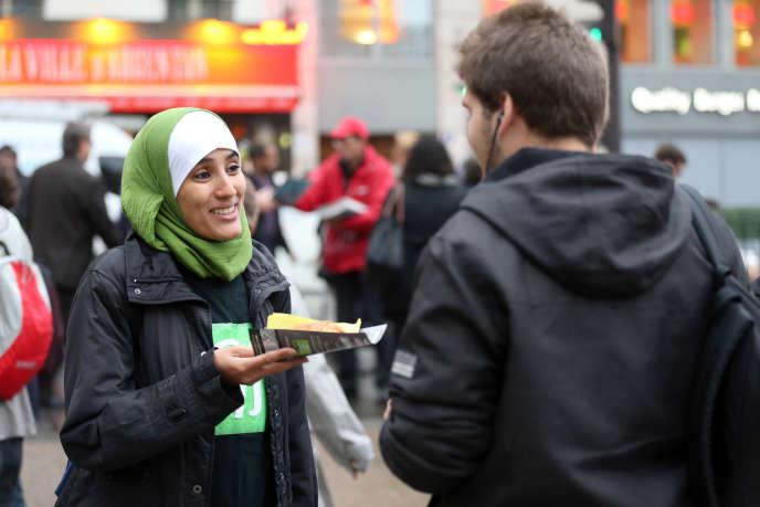 Une membre du Collectif contre l'islamophobie en France (CCIF) distribue des pains au chocolat en face de la gare Saint- Lazare, à Paris, en octobre 2012.