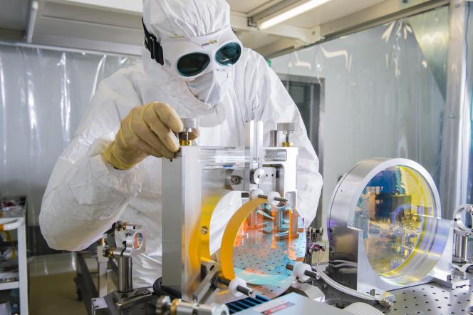 Manipulation en laboratoire d'un miroir de l'instrument Virgo, interféromètre qui permet de détecter des ondes gravitationnelles.