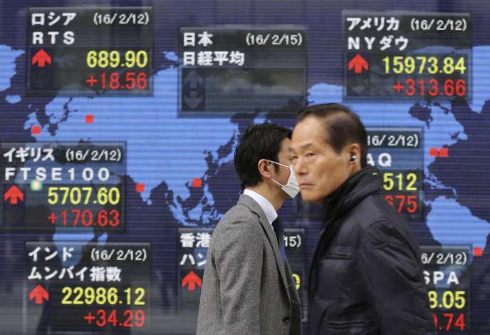 Des passants devant un panneau affichant les cours de la Bourse à Tokyo, en 2016.