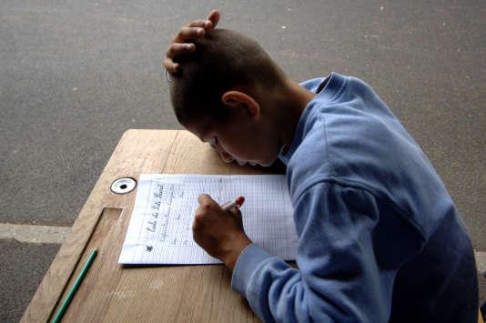 Un élève de CM2 écrit une dictée, en juin 2007 sous le préau de l'école primaire du Puits-Picard, à Caen.