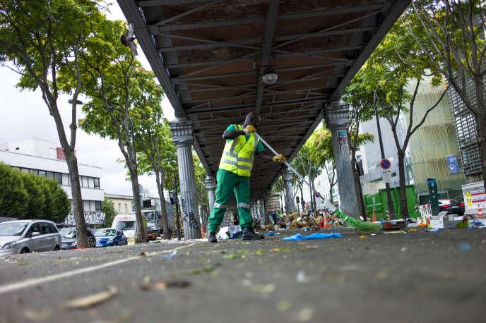 Un balayeur de l'unité«laFonctionnelle», une unité spéciale du département propreté de la ville de Paris, balaye une rue après un marché, en2014.