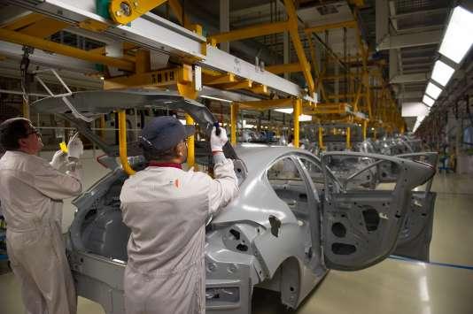 Des employés du constructeur automobile français PSA Peugeot Citroën dans l'atelier de peinture de l'usine de Mulhouse, le 29 avril 2015.