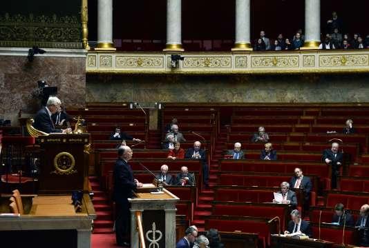 Le ministre de l'Intérieur Bernard Cazeneuse prend la parole  devant une Assemblée Nationale à moitié pleine, avant le vote de prolongation de l'état d'urgence le 16 février 2016 à Paris.