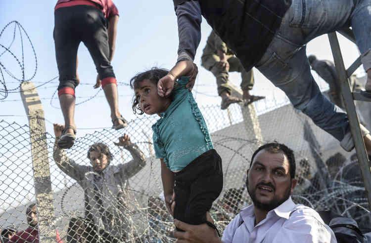 """Troisième prix, catégorie """"Actualités"""" (série). Des réfugiés syriens tentent de passer la frontière turque à Sianlurfa, le 14 juin. Le photographe turc Bulent Kilic suit régulièrement l'afflux de Syriens vers la Turquie."""