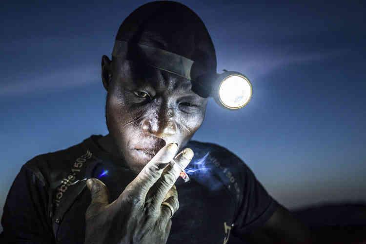 """Deuxième prix, catégorie """"Populations"""" (image seule). Un mineur profite de sa pause pour fumer une cigarette avant de retourner travailler, dans la mine de Bani, au Burkina Faso, le 20 novembre 2015. Dans cette mine, les travailleurs sont exposés à des métaux lourds et à des substances chimiques nocives."""