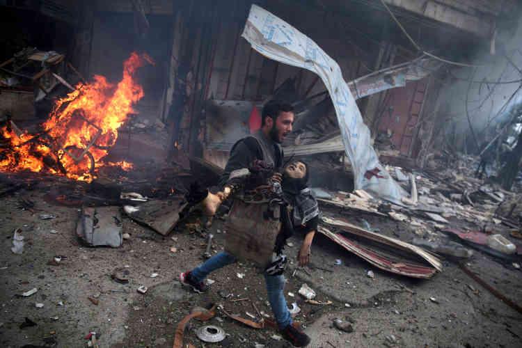 """Deuxième prix, catégorie """"Informations générales"""".  Un Syrien porte le corps sans vie d'un enfant, après un bombardement attribué à l'armée syrienne, dans la banlieue de Damas, le 7 novembre."""