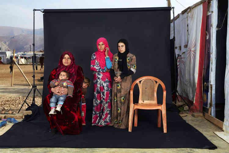 """Troisième prix, catégorie """"Populations"""". Portrait d'une famille syrienne posant dans un camp de réfugiés libanais, le 15 décembre. La chaise vide représente un des membres de la famille, disparu en Syrie."""