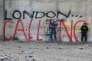 """Un migrant devant un graffiti dans la """"Jungle"""", à Calais, le 6 février 2016."""
