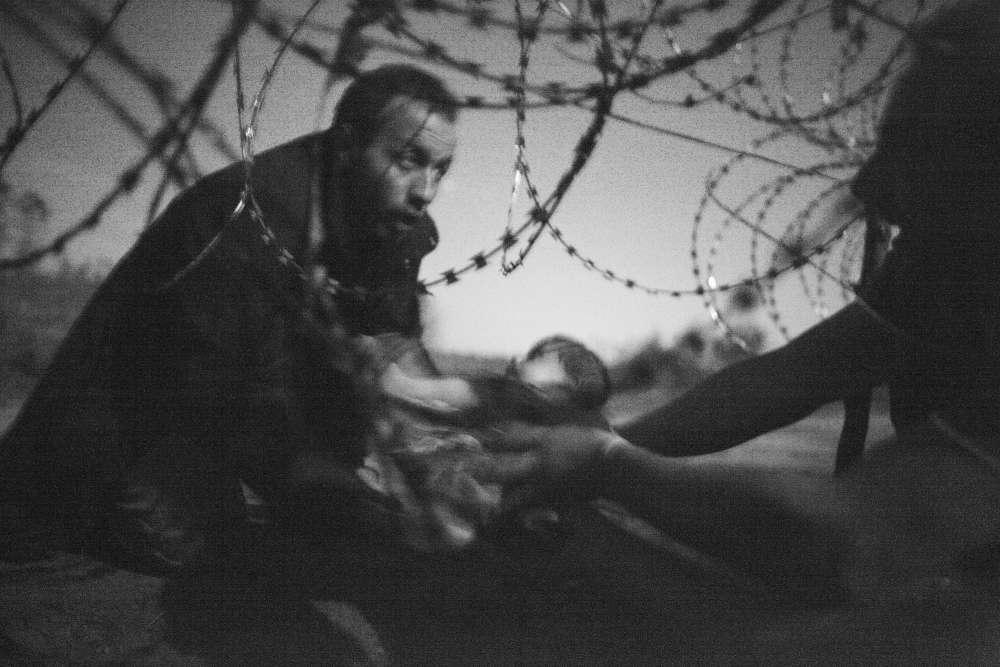 Premier prix, photo de l'année. Un homme tente de faire passer un bébé à travers la frontière séparant la Hongrie de la Serbie, le 28août 2015. «Je campais avec des réfugiés depuis cinq jours lorsqu'un groupe de 200 personnes est arrivé, raconte le photographe. Ils ont commencé à essayer de traverser la frontière, en tentant d'échapper à la police. Ça a duré plusieurs heures. J'ai pris cette image vers trois heures du matin, sans flash, pour éviter d'attirer les forces de l'ordre.»