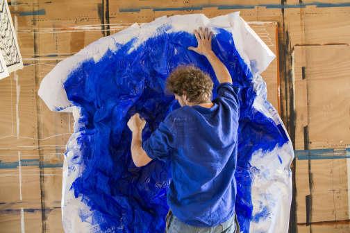 Alexandre Poulaillon, aux prises avec un papier peint pigmenté bleu laqué.