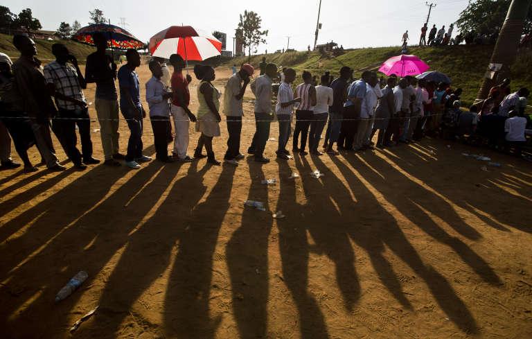 Des Ougandais font la queue devant un bureau de vote à Kampala pour voter lors du premier tour de la présidentielle,  jeudi 18 février 2016.