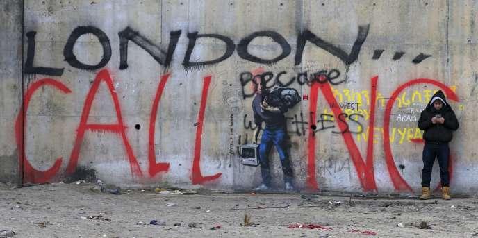 Un migrant devant un graffiti dans la
