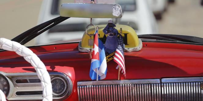 Drapeaux cubain et américain dans une voiture ancienne, à La Havane, en février 216.