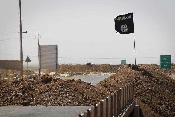 Un drapeau de l'Etat islamique de l'autre côté d'un pont sur le front des combats entre les forces kurdes des peshmergas et les militants islamistes dans Rashad, sur la route entre Kirkouk et Tikrit, en septembre 2014.