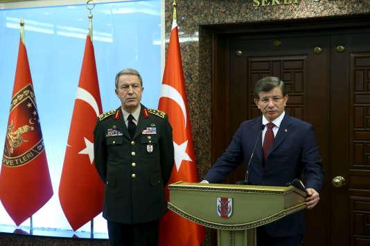 Le premier ministre turc, Ahmet Davutoglu, accompagné du chef d'état-major des armées, le général Hulusi Akar (à gauche), s'exprime devant la presse au siège de l'armée à Ankara, le 18 février.