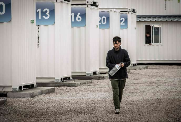 Un homme chemine dans le nouveau camp de conteneurs de Calais.