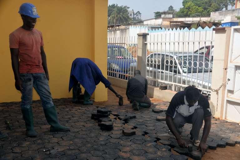 Des Camerounais couvrent le sol de pavés recyclés en déchets plastique à Yaoundé, le 1er février 2016.