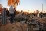 Des hommes inspectent des ruines dans un camp d'entraînement de l'organisation EI bombardé par des avions américains le 19 février 2016 près de Sabratha en Libye.