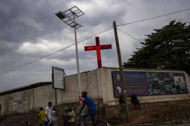 Des passants marchent sous la croix illuminée d'une église, le 25 janvier. La crainte d'un nouveau génocide, 21 ans après celui du Rwanda, a grandi au sein de la communauté internationale, préoccupée par les déclarations martiales des caciques du régime, et par les tensions entre communautés hutu et tutsi.
