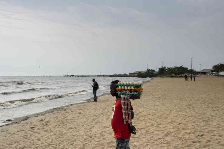 Un homme vend des œufs à la coque et des cacahuètes sur la plage publique du bord du lac Tanganyika, le 26 janvier. De l'autre côté du lac, à quelques kilomètres, se trouve la République démocratique du Congo, qui servirait de base arrière aux insurgés.