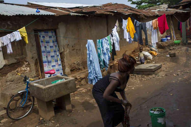 Une femme lave des vêtements, dans le quartier de Bwiza, le 25 janvier. En plus des 400 morts qu'ont déjà fait les affrontements,  près de 240 000 habitants du pays seraient partis en exil.