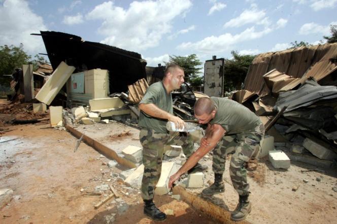 Deux soldats Français se lavent dans les débris du lycée Descartes de Bouaké,qui servait de camp militaire, le 10novembre2004. Neuf Français et un touriste américain ont été tués le 4novembre2004 lors d'un bombardement.