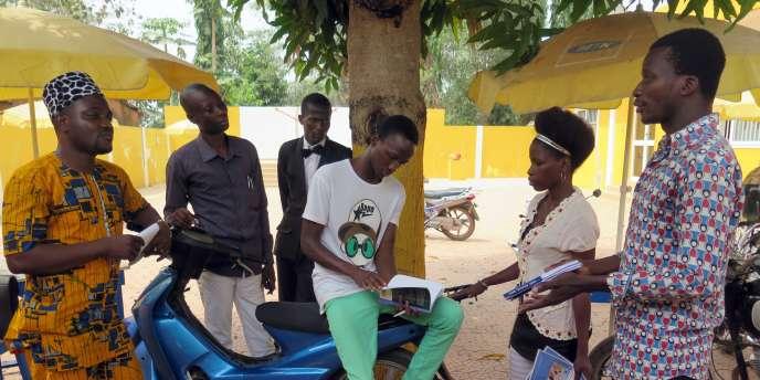 Des jeunes électeurs béninois lisent le livret distribué par une fondation allemande qui sensibilise à l'importance de ce scrutin.