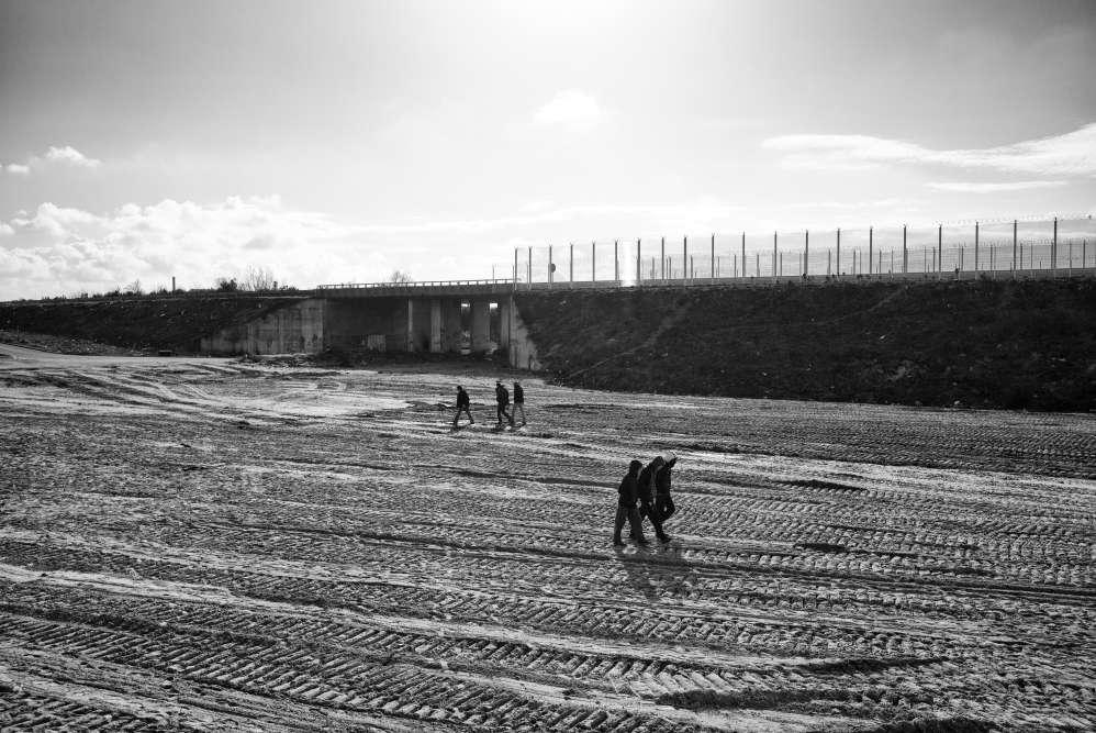 Calais, 22 février. Des réfugiés marchent dans la partie déjà rasée de la « jungle ».