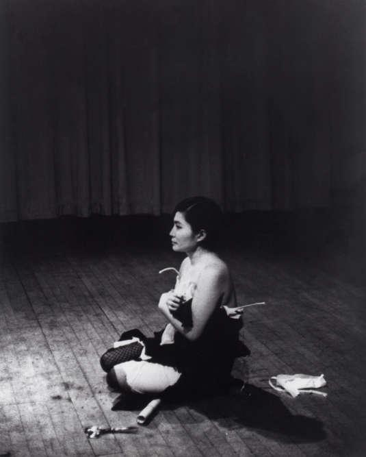 """« Cette performance a été réalisée pour la première fois par Yoko Ono le 20 juillet 1964, au Yamaichi Hall de Tokyo (Japon). L'artiste entre sur scène vêtue de sa plus belle robe, s'assoit dans une position traditionnelle japonaise, et invite le public à découper avec des ciseaux des morceaux de ses vêtements, qu'il peut emporter. Lors de certaines performances, elle a déclaré : """"Mon corps est la cicatrice de mon esprit."""" »"""