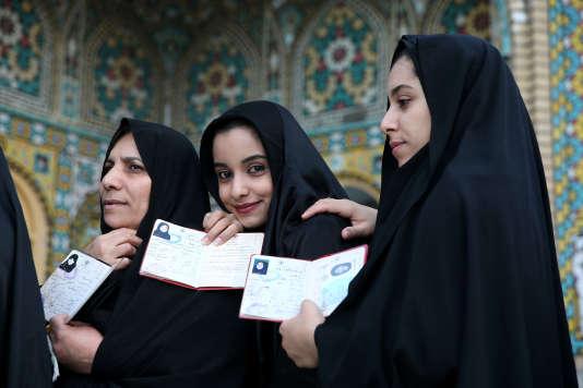 Des Iraniennes montrent leurs papiers d'identité avant d'aller voter pour les législatives et le renouvellement de l'Assemblée des experts, le 26 février, à Qom.
