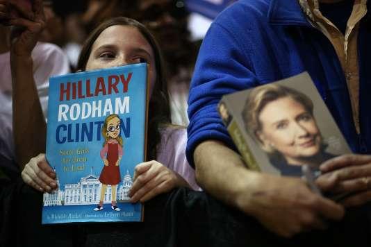 """Une fille brandit un livre intitulé """"Hillary Rodham Clinton. Certaines filles sont nées pour diriger"""", pendant un meeting de la candidate démocrate, à Fairfield (Alabama), le 27 février."""