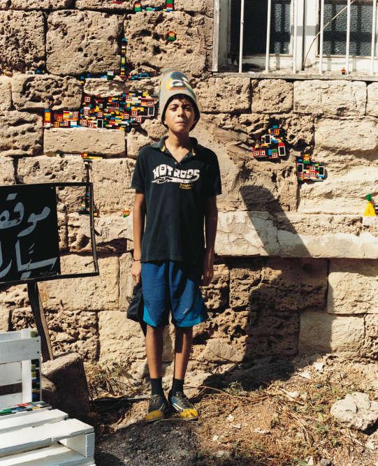 Un enfant pose devant une installation des artistes Pamela Haydamous et Léa Tasso qui forment le collectif Dispatch Beirut. Dans les trous laissés par des obus sur les immeubles, ils installent, comme une forme de restauration, des Lego : « Nous cherchons à remplacer les stigmates de la guerre par de la couleur et des souvenirs joyeux. Ainsi nous construisons notre propre Beyrouth », souligne Pamela Haydamous.