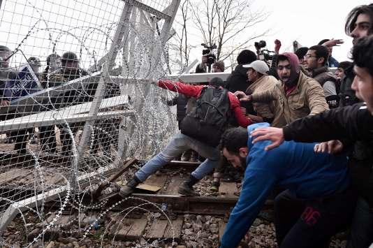 Les migrants tentent de briser une barrière à la frontière avec la Macédoine près du village grec d'Idomeni, le 29 février, où plus de 7 000 personnes sont bloquées, alors que la colère monte en raison des restrictions sur les déplacements des migrants.