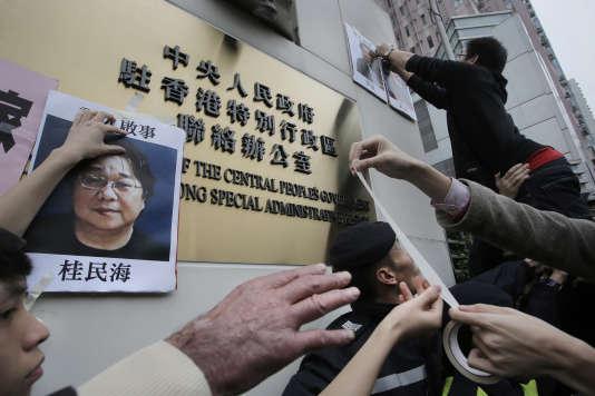 Des manifestants essaient d'afficher des portraits des éditeurs disparus lors d'un rassemblement de protestation le 3 janvier devant le Bureau de liaison de Pékin à Hongkong.